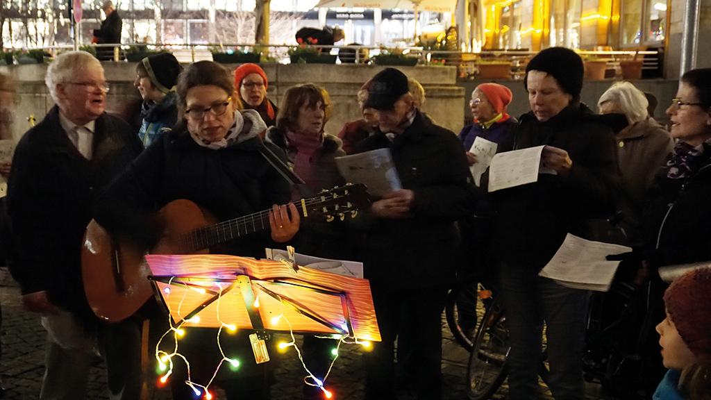 Singen am Abend vor der Thomaskirche im Schein der Lichterketten