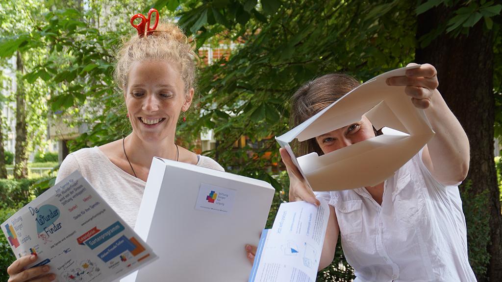 Zwei Mitarbeiterinnen mit Aufklebern, Faltschachteln etc. aus dem Anlasspendenset im Grünen vorm Stiftungsbüro