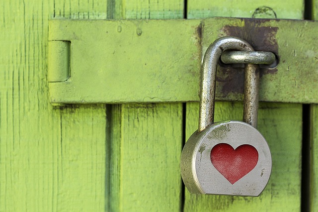 Tür mit Vorhängeschloss auf dem ein Herz anbebildet ist