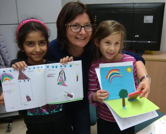 Patin mit ihren zwei Patenkindern zeigen ihre Exkursionstagebücher