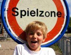 Junge vor Schild mit Aufschrift Spielzone