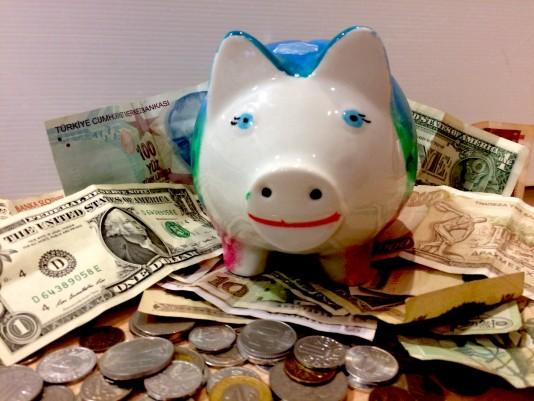 Glückliches Sparschwein auf ausländischen Münzen und Scheinen
