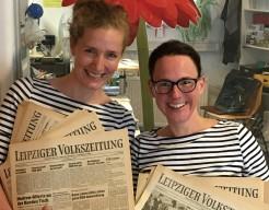Zwei Mitarbeiterinnen mit historischen Ausgaben der LVZ
