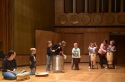 Kinder und Paten im Gewandhaus beim Trommeln auf der Bühne