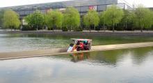Stifter im Quandem (vierrädriges Fahrrad mit Dach) durchqueren die Wasserfläche vor der Glashalle der Leipziger Messe. Foto: Axel Halling, Berlin
