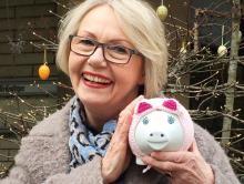 Katrin Hart mit einem rosa umhäkelten Sparschwein vor einem Osterstrauch