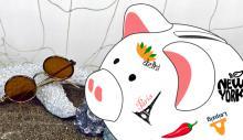 Sparschwein mit Aufklebern verschiedener Städte vor Sonnenbrille, Muscheln und Fischernetz