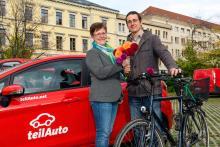 Angelika Kell begrüßt Michael Creutzer mit Blumen, im Hintergrund Fahrzeuge von teilAuto an der Harkortstraße in Leipzig