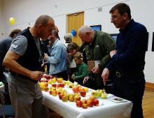 Obstgenosse Berninger im Gespräch mit Thilo Egenberger. Stehen am Tisch mit vielen Apfelsorten