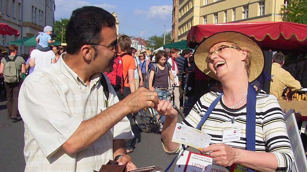 Mahmoud Dabdoub kauft ein Los der Bürgerlotterie bei Katrin Hart. Straßenfest Connewitz 2009.