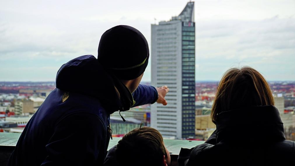 Ein Patenteam blickt vom Rathausturm hinüber zum Uniriesen