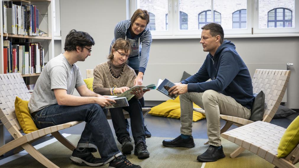 Gruppe im LeipzigZimmer, sitzt in Lounge-Sesseln und diskutiert