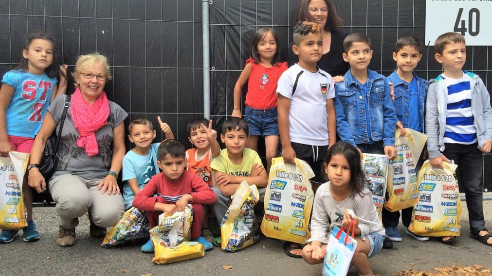 geflüchtete Kinder und zwei Mitarbeiterinnen der Stiftung Bürger für Leupzig mit den übergebenen Spenden