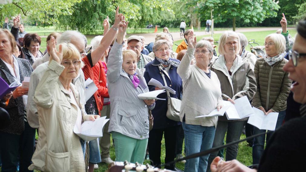 Bürgersänger/innen im Halbkreis, einige zeigen mit dem erhobenen Arm, dass neu dazu gekommen sind