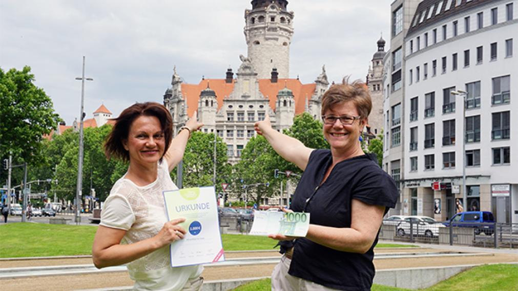Frau Bellmann überreicht Angelika Kell vor dem Rathaus die Preisurkunde